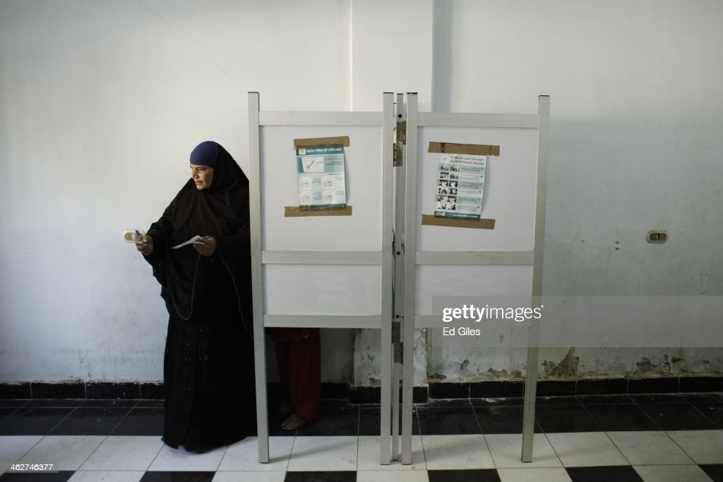 An Egyptian woman casts her vote at a polling booth on January 15, 2014 in the rural district of Fayoum, Egypt. Egyptians went to the polls for a second day today, after the first day of voting yesterday was marred by clashes between protesters and security forces, and one explosion at a courthouse, in the Egyptian capital Cairo. Egyptians are voting to decide on the third constitution for Egypt since the overthrow of former President Hosni Mubarak in February 2011.