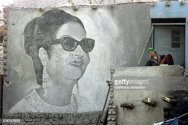 An Egyptian woman collects clothes in front of a giant picture of Egyptian diva Umm Kulthum painted on her shack in the impoverished Kom alGhurab...
