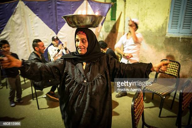 An Egyptian woman dancing during a henna night on the street of Shubra in Cairo Egypt on December 18 2014 Egyptians living unpaved outskirts Cairo...