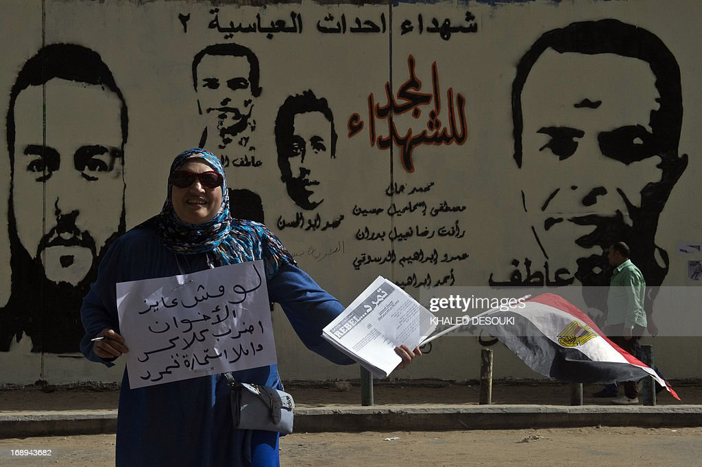 An Egyptian woman distributes a sheet of Tamarod (rebellion) campaign try to collect signatures to demand the ouster of Egyptian President Mohamed Morsi and for early presidential elections in Cairo on May 17, 2013. Hundreds of people marched on Cairo's Tahrir Square calling for Morsi to resign and demanding early elections, AFP correspondents and local media reported.