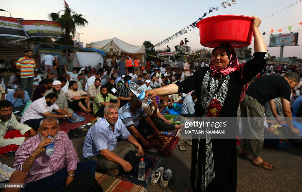 An Egyptian woman distributes water to supporters of the Muslim Brotherhood and of Egypt's ousted president Mohamed Morsi as they break their fast outside Cairo's Rabaa al-Adawiya mosque on July 11, 2013, during the second day of Islam's holy fasting month of Ramadan. The people of Egypt are marking the Muslim fasting month of Ramadan amid soaring tensions following last week's ouster by the military of Islamist president Mohamed Morsi.