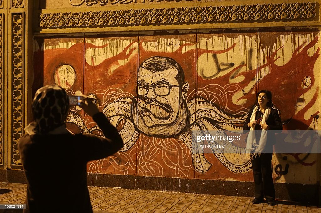 An Egyptian woman has her photo taken in front of graffiti portraying Egyptian President Mohamed Morsi during demonstration outside the presidential palace on December 9, 2012 in Cairo. Egypt's opposition called for mass street protests rejecting a December 15 referendum on a new constitution largely drafted by President Mohamed Morsi's Islamist allies. AFP PHOTO/PATRICK BAZ