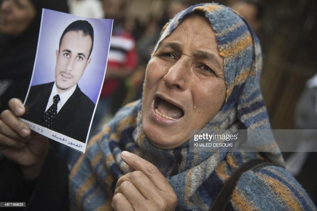 An Egyptian woman holding the portrait of a relative reacts outisde the court that sentenced 682 alleged Islamists and a Muslim Brotherhood leader to...