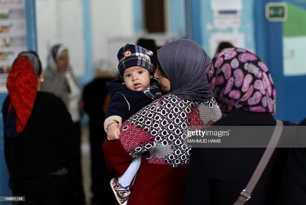 An Egyptian woman holds her child at a polling station during the second round of a referendum on a new draft constitution in Giza, south of Cairo, on December 22, 2012. Egyptians are voting in the final round of a referendum on a new constitution championed by President Mohamed Morsi and his Islamist allies against fierce protests from the secular-leaning opposition.