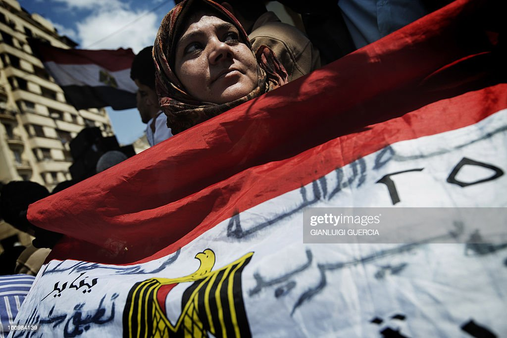 An Egyptian woman holds her national flag during a demonstration held by thousands of Muslim Brotherhood supporters in front of the High Court in Cairo demanding a purge in the Egyptian judicial system on April 19, 2013. AFP PHOTO/GIANLUIGI GUERCIA