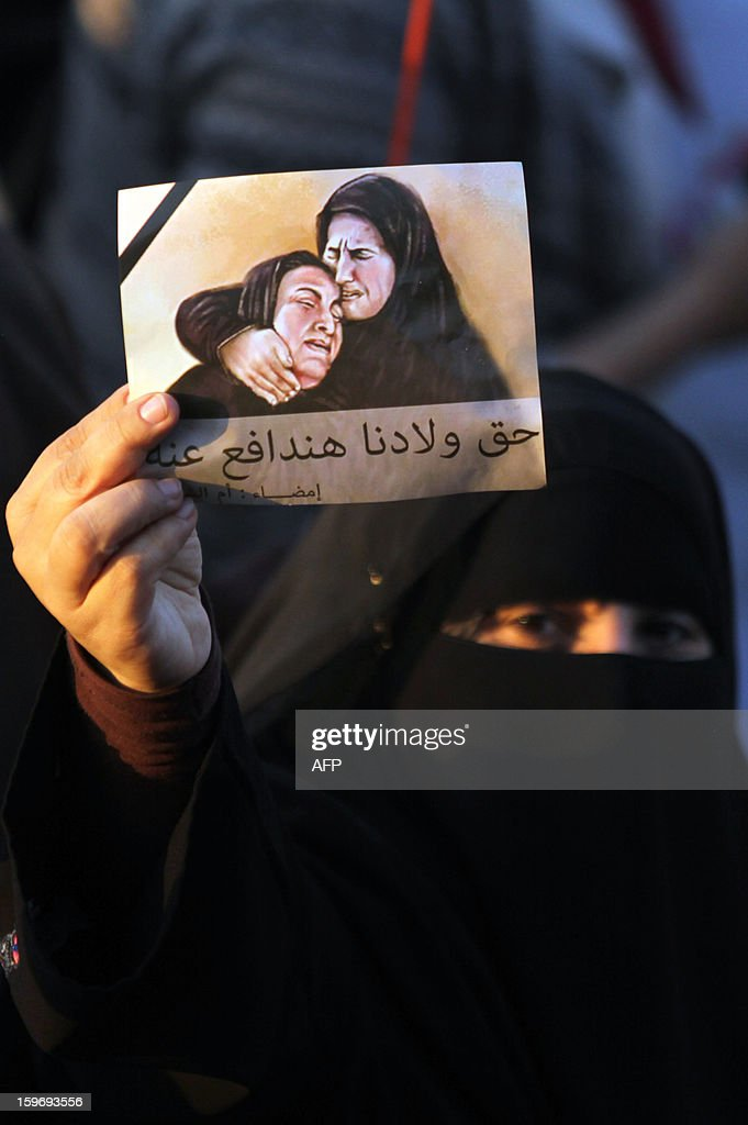An Egyptian woman holds up a picture during a demonstration demanding justice for the victims of the 2012 Port Said football match killings, one week ahead of a court ruling on the matter, in Cairo's Tahrir square on January 18, 2013. Thousands of supporters of Al-Ahly club demonstrated in Cairo on Friday to demand severe punishments for 75 people on trial for dozens of deaths in Egypt's worst football disaster.