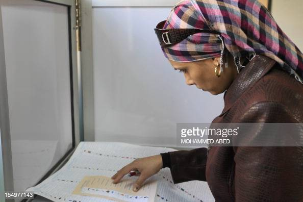 An Egyptian woman inspects her ballots at a polling station in Cairo on December 15 on the second day of the second round of parliamentary voting...