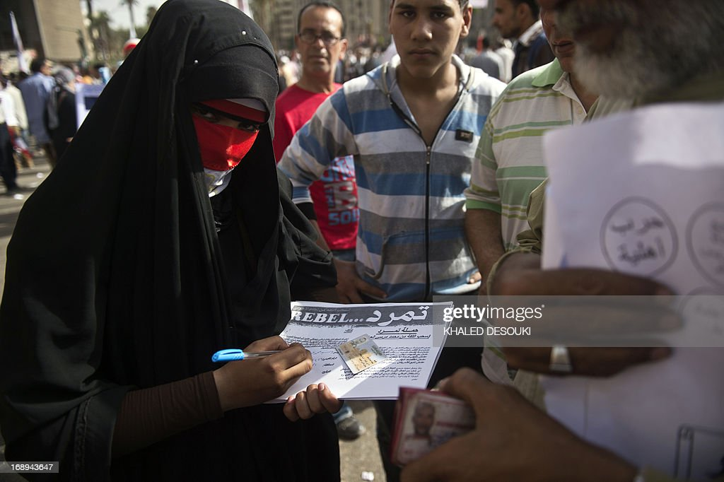 An Egyptian woman part of the Tamarod (rebellion) campaign to demand the ouster of Egyptian President Mohamed Morsi and for early presidential elections, fills out a sheet for a bystander in Cairo on May 17, 2013. Hundreds of people marched on Cairo's Tahrir Square calling for Morsi to resign and demanding early elections, AFP correspondents and local media reported.
