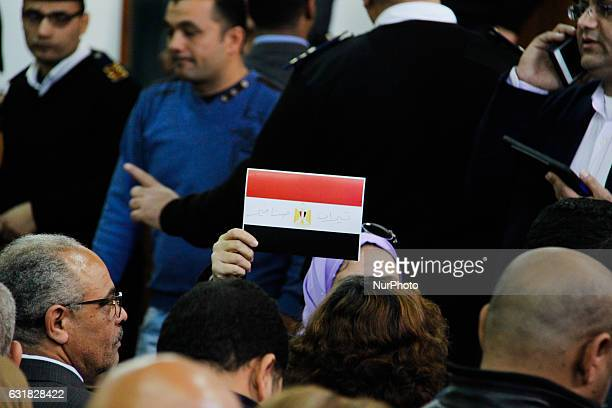 An Egyptian woman raises a card in a courthouse showing the national flag defaced with the words quotTiranquot and quotSanafirquot after the High...