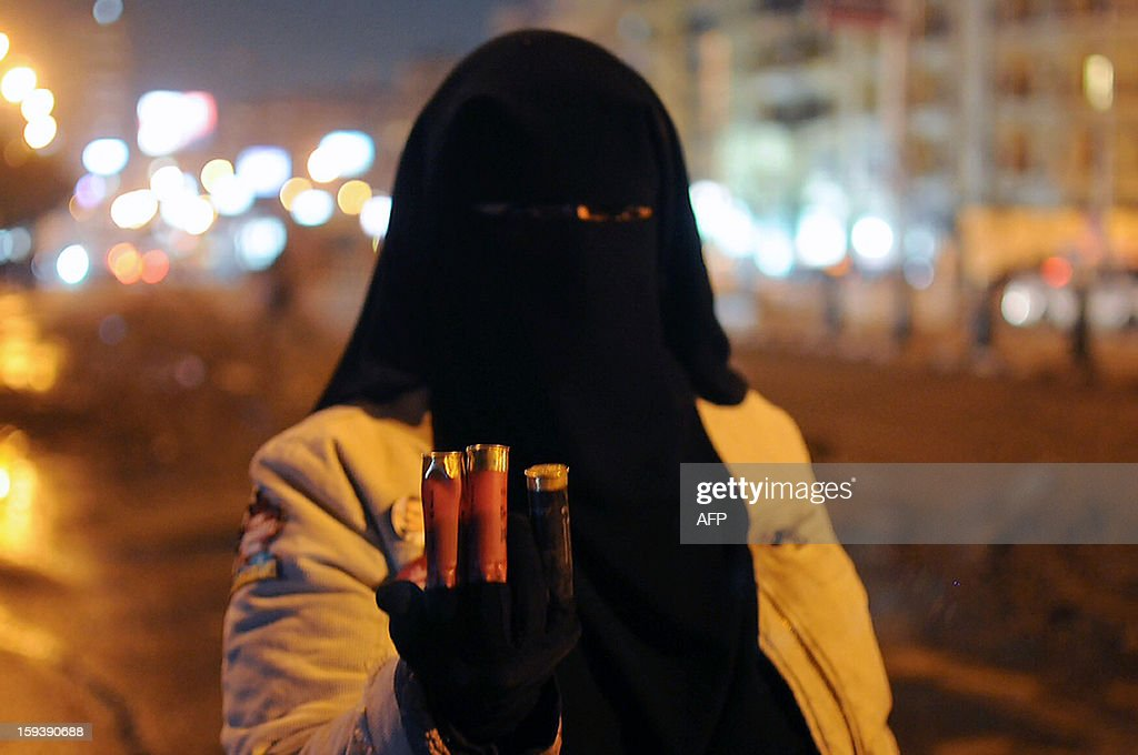An Egyptian woman shows spent bullet casings after masked gunmen attacked protesters camped outside the presidential palace in Cairo late on January 12, 2013. The gunmen hurled firebombs at tents of protesters -- opponents of Islamist President Mohamed Morsi -- and fired birdshot in clashes that left policemen and civilians injured, a security official said. AFP PHOTO/NAMEER GALAL