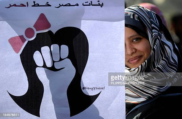 An Egyptian woman stands behind a poster reading 'Egypt's girls are a red line' in Cairo's Tahrir Square on December 23 2011 as people gathered for a...