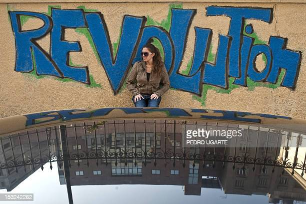 An Egyptian woman stands in front of graffiti reading 'Revolution' at Cairo's Tahrir Square the epicentre of the popular revolt that drove veteran...