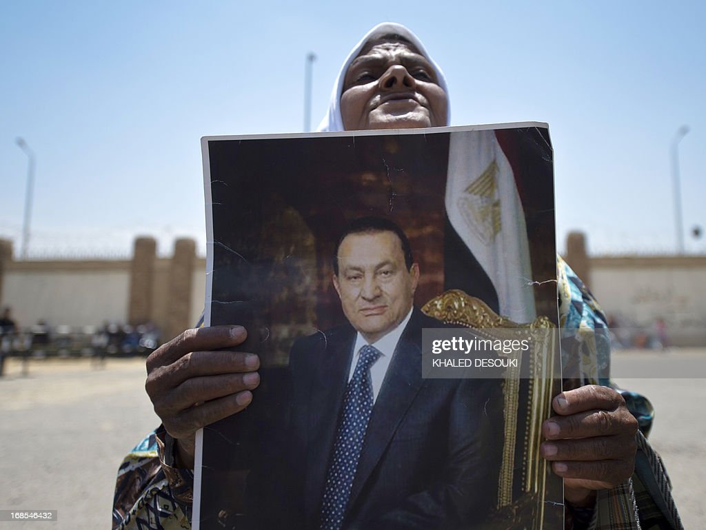 An Egyptian woman supporter of former Egyptian president Hosni Mubarak, holds a portrait of him outside the Egyptian police academy in Cairo, where Mubarak's trial is taking place on May 11, 2013. Mubarak appeared in court to face a new trial for complicity in the murder of hundreds protesters during the 2011 uprising. AFP PHOTO / KHALED DESOUKI