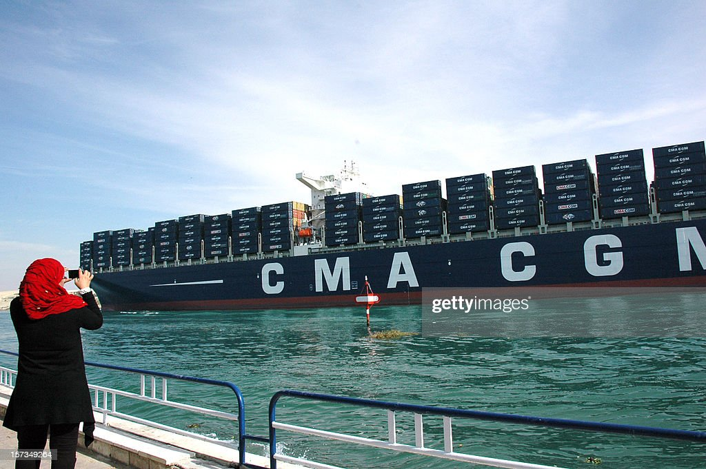 An Egyptian woman takes a photo of the largest and the newest container ship in the world, the British flagged CMA CGM Marco Polo, sails through the Suez Canal on December 2, 2012, as it passes the port of Ismailia, 120 km northeast of the Egyptian capital Cairo. The South Korean built Marco Polo can carry some 16 000 containers or 167 000 tons. AFP PHOTO/STR