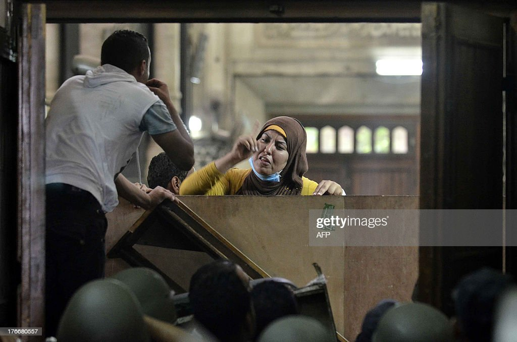 An Egyptian woman talks to policemen from the inside of Cairo's Al-Fath mosque where Islamist supporters of ousted president Mohamed Morsi hole up on August 17, 2013. The standoff at al-Fath mosque in central Ramses Square began on August 16, with security forces surrounding the building where Islamists were sheltering and trying to convince them to leave.