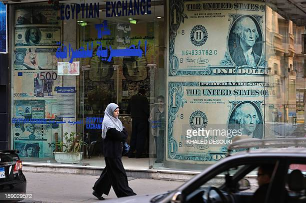 An Egyptian woman walks past an exchange store in the capital Cairo on January 6 2013 A top International Monetary Fund official will visit Egypt on...