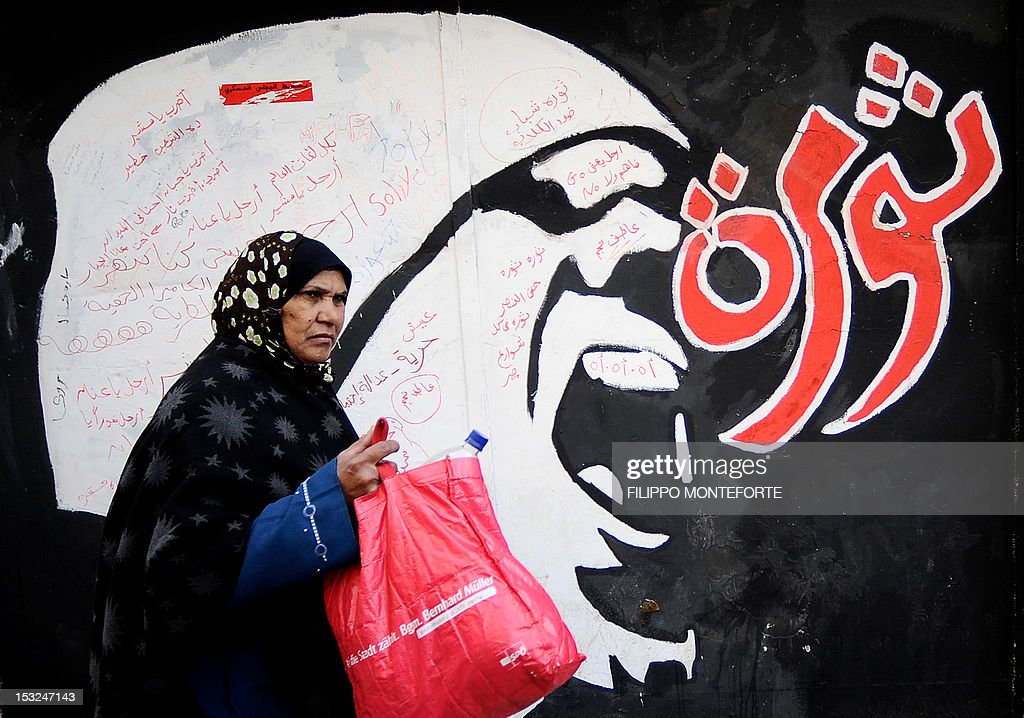 An Egyptian woman walks past graffiti reading 'Revolution' outside the American University off Tahrir Square in Cairo on December 21 2011 Egyptians...