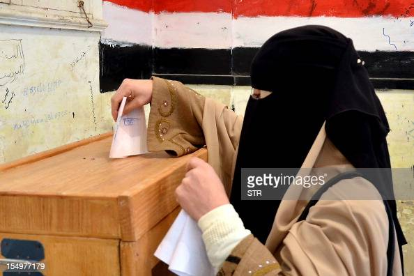 An Egyptian woman wearing a niqab casts her ballot at a polling station in Damanhur in the coastal governorate of Buhaira on December 14 2011...