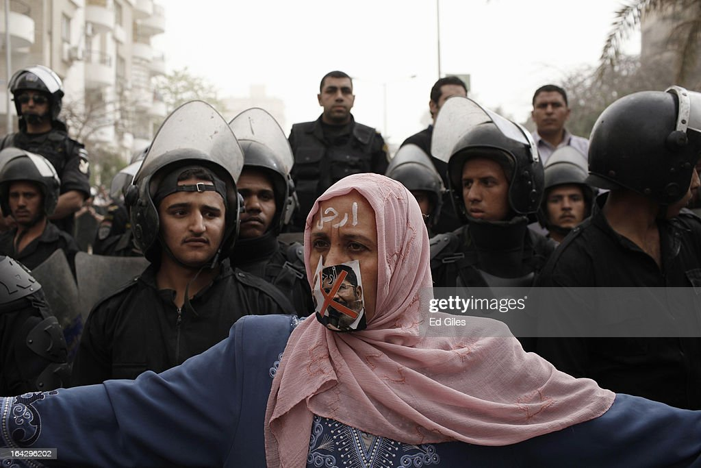 An Egyptian woman with a picture of President Mohammed Morsi over her mouth stands before a line of riot police during a demonstration at the headquarters of the Muslim Brotherhood on March 22, 2013 in Cairo, Egypt. Opposition demonstrators converged on the headquarters of the Muslim Brotherhood in the Cairo suburb of Muqattam to protest against the government of President Mohammed Morsi, who is closely connected to the Muslim Brotherhood movement.