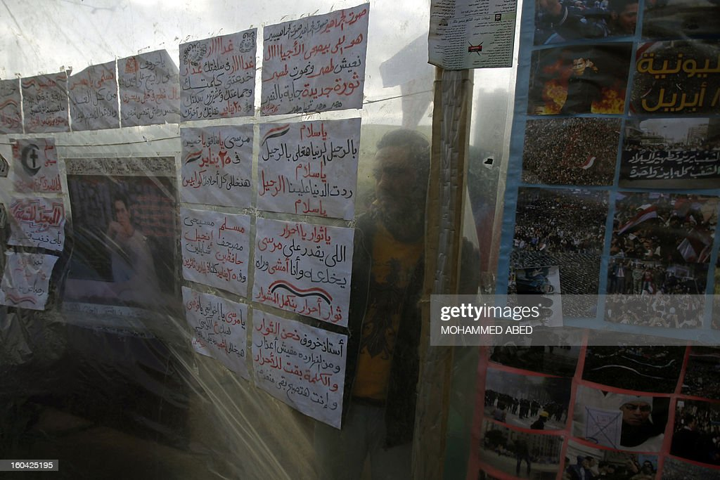 An Egyptian youth looks at slogans against Egypt's President Mohamed Morsi that are hanging in Cairo's Tahrir Square on January 31, 2013. Rival factions in Egypt condemned the violence which has killed dozens in a week of unrest and pledged support for a national dialogue to resolve the political crisis gripping the country. AFP PHOTO/MOHAMMED ABED
