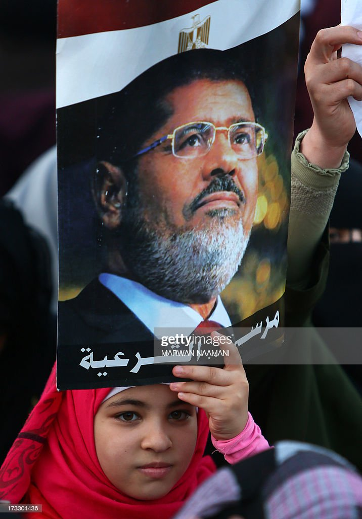 An Egyptian youth, supporter of the Muslim Brotherhood and Egypt's ousted president Mohamed Morsi carries a poster of him as worshipers gather for a dusk payer outside Cairo's Rabaa al-Adawiya mosque on July 11, 2013, during the second day of Islam's holy fasting month of Ramadan. The people of Egypt are marking the Muslim fasting month of Ramadan amid soaring tensions following last week's ouster by the military of Islamist president Mohamed Morsi.