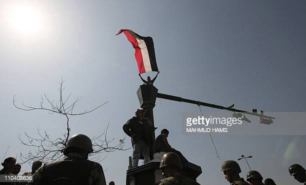An Egyptian youth waves his national flag while standing on a traffic light pole during a protest at Tahrir Square in Cairo on March 18 2011 as...