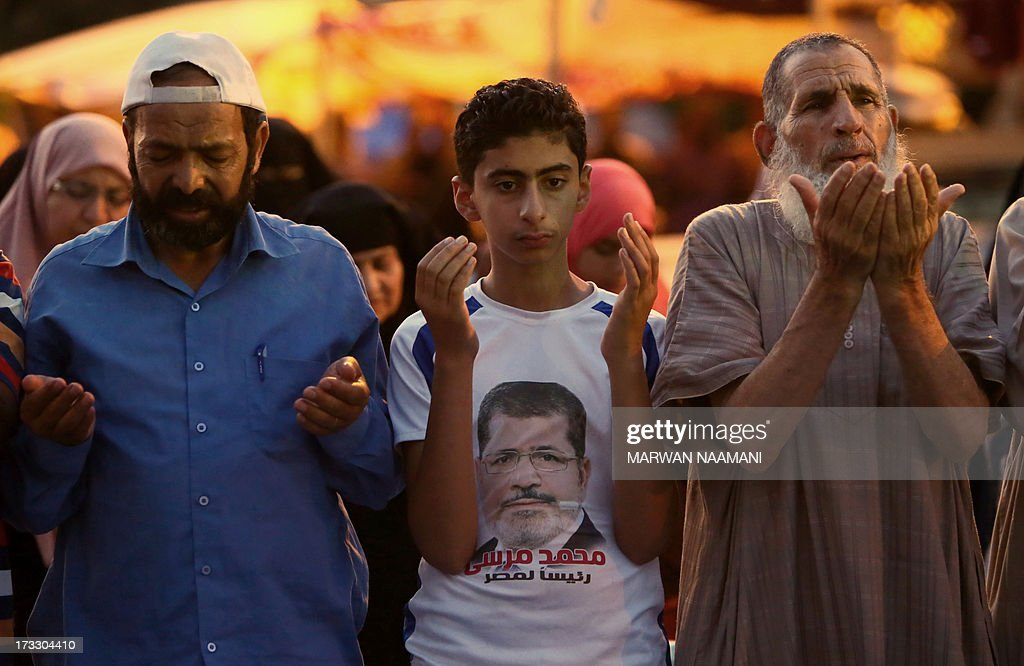 An Egyptian youth wears a shirt with a portrait of ousted president Mohamed Morsi as he performs a prayer among supporters of the Muslim Brotherhood outside Cairo's Rabaa al-Adawiya mosque on July 11, 2013, during the second day of Islam's holy fasting month of Ramadan. The people of Egypt are marking the Muslim fasting month of Ramadan amid soaring tensions following last week's ouster by the military of Islamist president Mohamed Morsi.