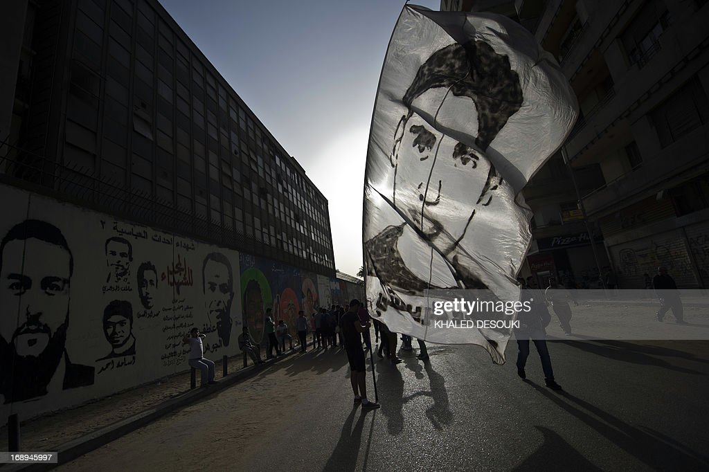 An Egyptians man holds a portrait commemorating those who died during the 2011 uprising, in Tahrir square in Cairo on May 17, 2013 during a demonstration calling for the ouster of Egyptian President Mohamed Morsi and for early presidential elections.