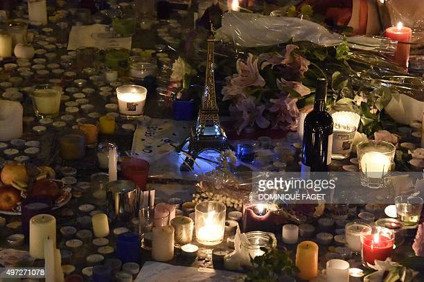 An Eiffel tower figurine and a bottle of red wine are pictured among lit candles and flowers at a makeshift memorial in front of 'Le Carillon'...