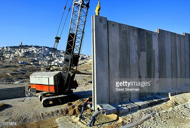 An eightmeter high concrete barrier is put into place as Israeli workers build Israel's separation wall November 30 2003 that will cut the West Bank...