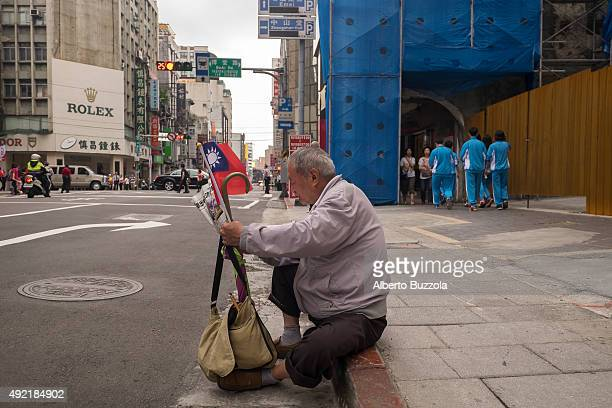 An elder man holding the Republic of China flag reads the newspaper after having attended the annual celebration of the ROC birthday which occurs on...