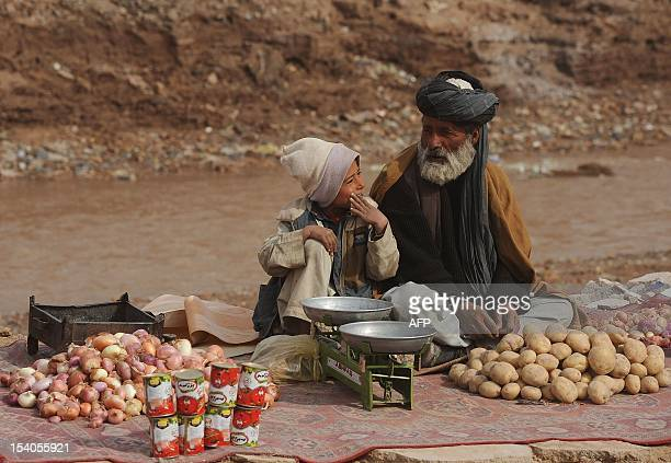An elderly Afghan vendor with his son waits for customers in the city of Herat on February 16 2012 Poverty and an ongoing insurgency by the ousted...