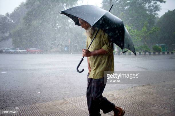 UNIVERCITY DHAKA BANGLADESH An elderly Bangladeshi man walk in heavy rain in Dhaka city Recent heavy rainfall caused flooding in several areas of the...