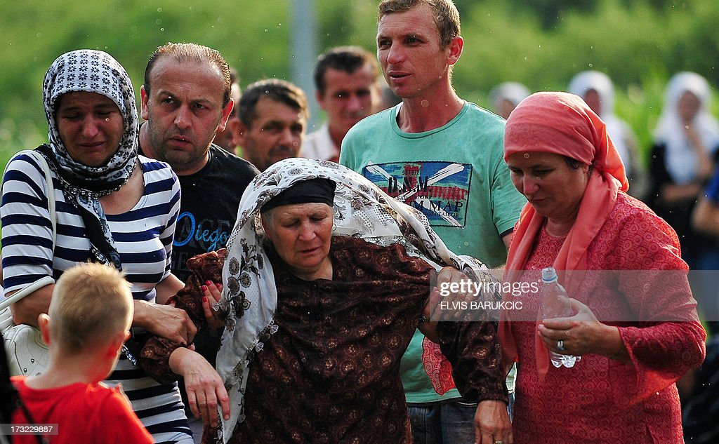 An elderly Bosnian Muslim woman, survivor of Srebrenica 1995 massacre, is helped to a medical station after she passed out, at memorial cemetery in village of Potocarion near Eastern-Bosnian town of Srebrenica, on July 10, 2013. Potocari Memorial cemetery is undergoing preparations for another mass burrial on July 11, when 409 newly identified bodies will be put to final rest. Bodies are identified as those belonging to Bosnian Muslim victims, of the offensive undertaken by Bosnian Serbs in July 1995 with aim to occupy, earlier declared UN safe heaven area of Srebrenica and the surrounding villages. During the offensive more than 8000 Bosnian non-Serbs went missing to be found burried in mass graves, years after the war ended.