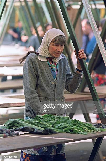 An elderly Bosnian woman sells salad leaves at the market in Sarajevo on September 5 1992 As the siege of the city continues food supplies run low...
