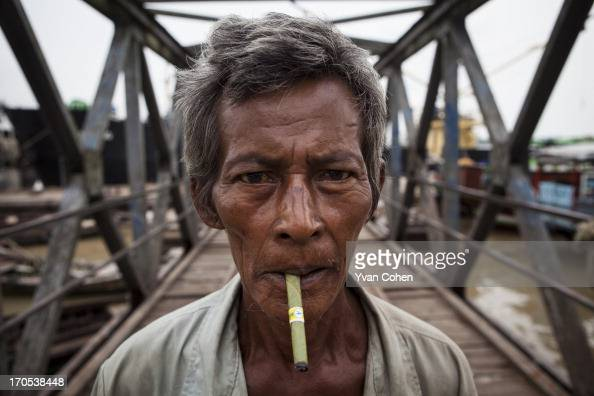 An elderly Burmese worker smokes a cheroot as he walks across a jetty at one of the dock areas in Yangon