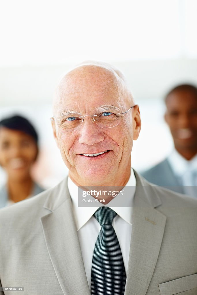 An elderly business man smiling with his team at back : Stock Photo