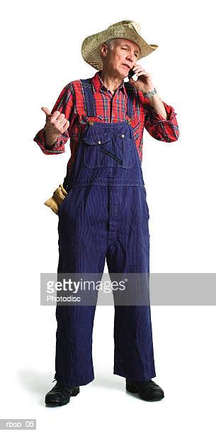 an elderly caucasian farmer chats on his cell phone