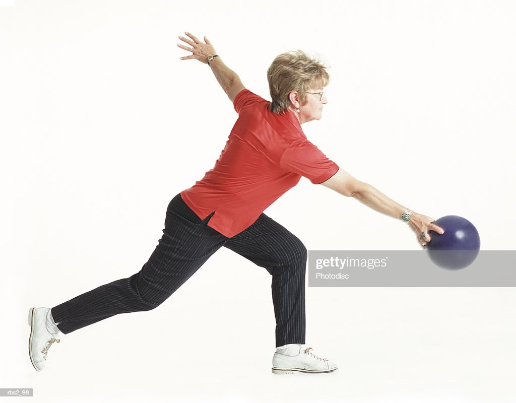 an elderly caucsian woman with light brown hair wearing a red bowling shirt is running forward about to throw her blue bowling ball