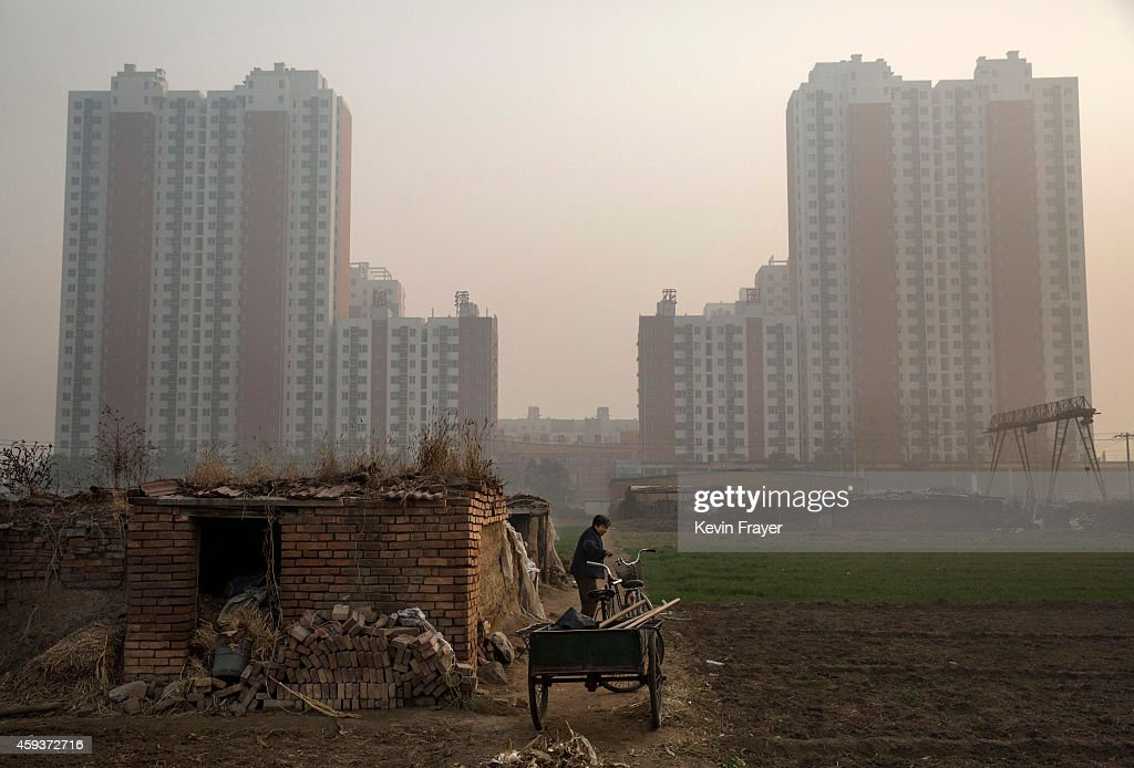 An elderly Chinese farmer stands outside her home on farmland backdropped by a new housing development on November 21 2014 in Hebei just outside...