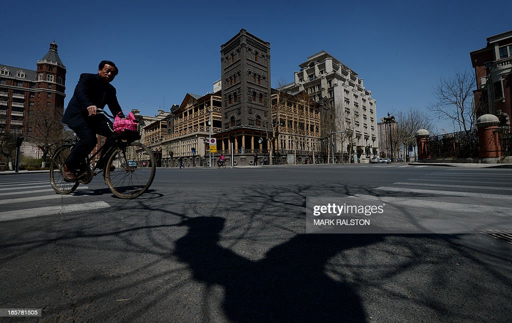 An elderly Chinese man rides his bike past the historic Astor Hotel in the recently renovated foreign concession area of Tianjin on April 6, 2013. The 150 year old hotel was first international hotel ever built in China and was recently restored to its original condition. AFP PHOTO/Mark RALSTON