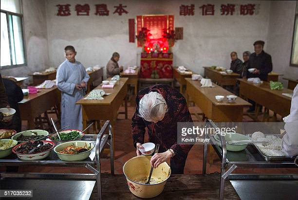 An elderly Chinese resident serves herself food during lunch at the Ji Xiang Temple and nursing home on March 18 2016 in Sha County Fujian province...