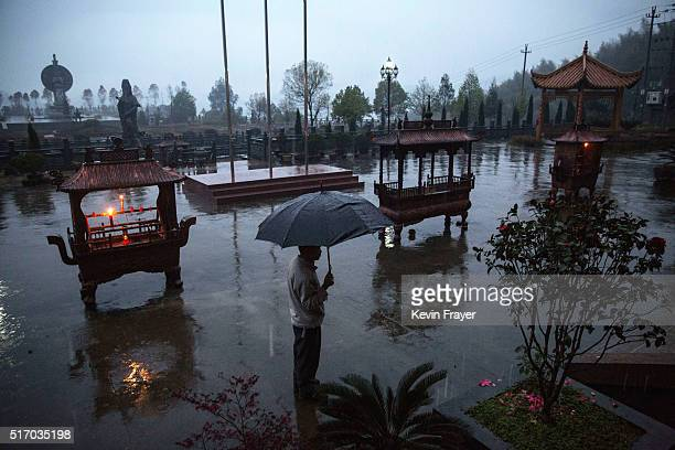 An elderly Chinese resident stands in the rain at the Ji Xiang Temple and nursing home on March 18 2016 in Sha County Fujian province China The...