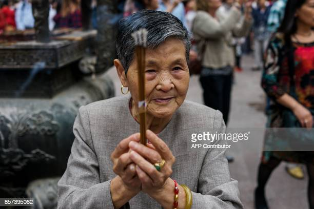 An elderly Chinese woman holds joss sticks as she prays at the Jing'an Temple during the midautumn festival in Shanghai on October 4 2017 / AFP PHOTO...