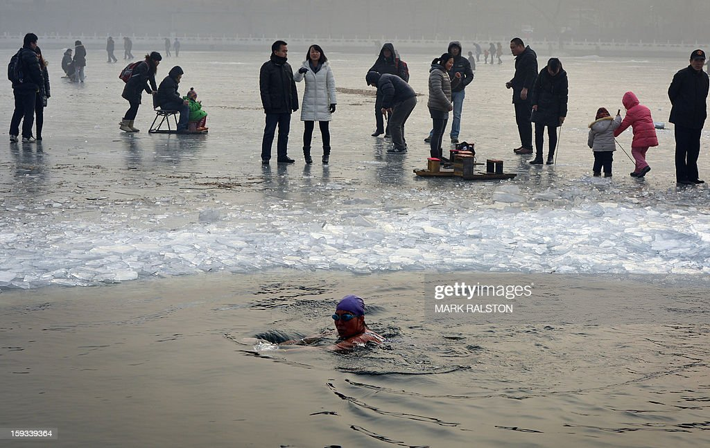 An elderly Chinese woman (C) swims in the frozen Houhai Lake in Beijing on January 12, 2013. Winter swimming is especially popular amongst the elderly and retired as it is believed to improve circulation and benefit health, and also said to increase the level of mental awareness, release stress, remove aches and pains, increase vitality and keep skin looking younger. AFP PHOTO/Mark RALSTON