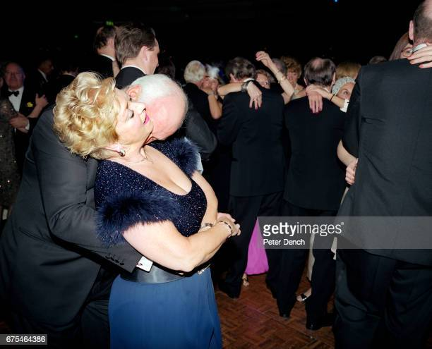An elderly couple are intimate on the dance floor at a charity function hosted at the Dorchester Hotel located on London's upmarket Park Lane May 2001