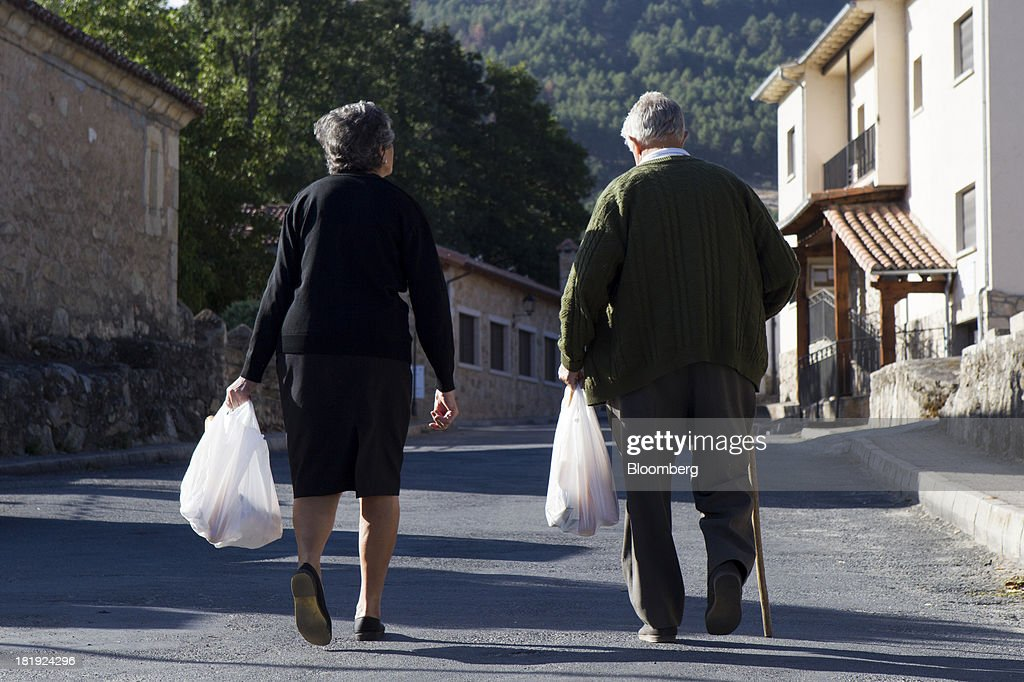 An elderly couple carry shopping bags along a main street in Bohoyos, Spain, on Thursday, Sept. 26, 2013. Prime Minister Mariano Rajoy is increasingly dependent on the pension reserve fund as it reaps lower returns on Spanish sovereign debt, which comprise 97.5 percent of its investments. Photographer: Antonio Heredia/Bloomberg via Getty Images