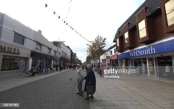 An elderly couple cross the main shopping precinct outside a WH Smith store in Lowestoft UK on Tuesday Oct 9 2012 UK Chancellor of the Exchequer...