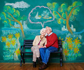 An elderly couple daydreaming on a park bench.