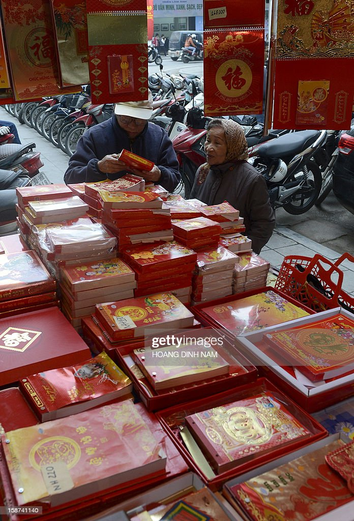 An elderly couple inspect 2013 calendars on sale in front of a book store in downtown Hanoi on December 27, 2012. Vietnamese traditionally utilize calendars, allowing them to consult not only the western calendar but also the lunar calendar for important personnel and cultural events. AFP PHOTO/HOANG DINH Nam